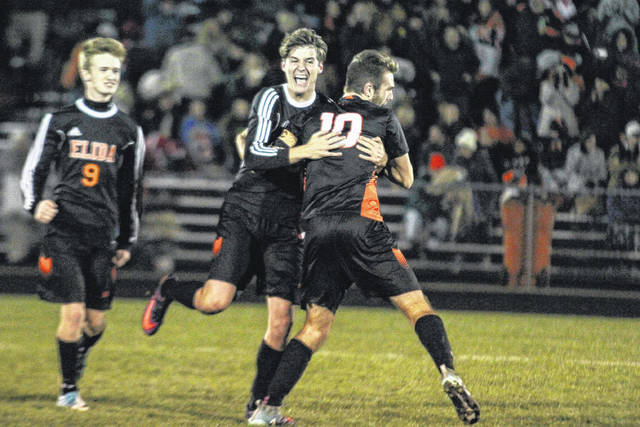 Elida's Sebastian Kunkleman (9), Jake Taylor (10) and Max Parkercelebrate after the Bulldogs clinched the Division II district championship Thursday night against Kenton at the Elida Athletic Complex.