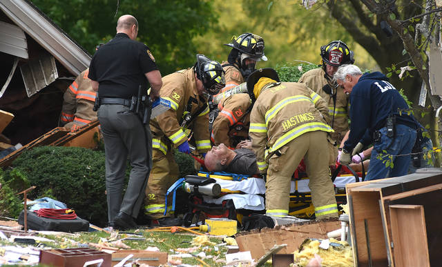 Firefighters help Jim Mauk from his destroyed home at 4230 Slabtown Road in Bath Township on Monday morning. He suffered a fractured right femur, fractured wrist, broken back, fractured left fibula and tibia and multiple rib fractures, his son Scott Mauk said.