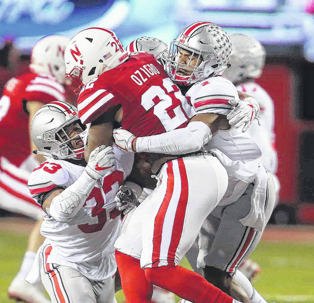 Ohio State's Dante Booker (33) and Damon Webb combine to tackle Nebraska's Devine Ozigbo during Saturday night's game at Memorial Stadium in Lincoln, Neb. See more game photos at LimaScores.com.