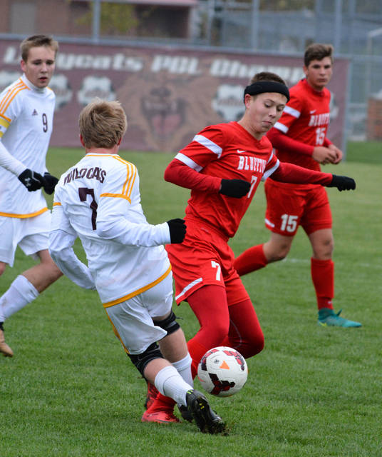 Kalida's Matt Keheres hits the ball off the leg of Bluffton's Luke Young during Saturday's Division III soccer district final in Kalida.