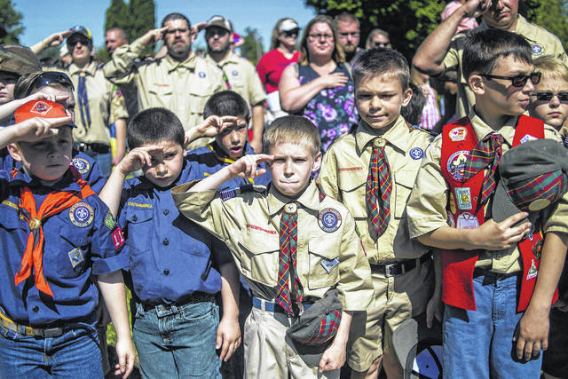 FILE - In this Monday, May 29, 2017 file photo, Boy Scouts and Cub Scouts salute during a Memorial Day ceremony in Linden, Mich. On Wednesday, Oct. 11, 2017, the Boy Scouts of America Board of Directors unanimously approved to welcome girls into its Cub Scout program and to deliver a Scouting program for older girls that will enable them to advance and earn the highest rank of Eagle Scout.