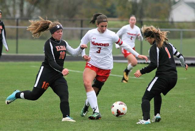 Wapakoneta's Abbi Ruppert (3) attempts to get up field while being defended by Elida's Micah Wassink (16) and Baylie Moening during Saturday's Division II district final at Elida.