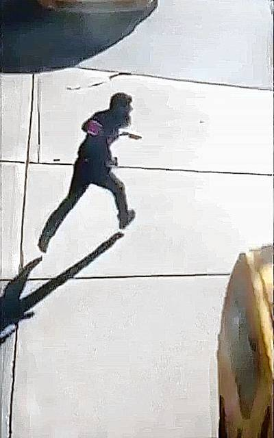 This image made from a video provided by Tawhid Kabir shows the suspect in a deadly attack running across the street with a fake gun in each hand on Tuesday, Oct. 31, 2017, in New York. The man mowed down pedestrians and cyclists along a busy bike path near the World Trade Center memorial on Tuesday, before he was shot in the abdomen by police after jumping out of the truck, authorities said. (YouTube/Tawhid Kabir via AP)