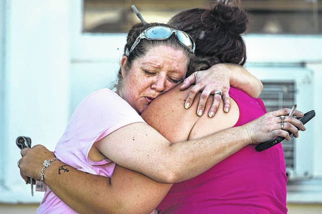 Carrie Matula, formerly of Waynesfield embraces a woman after a fatal shooting at the First Baptist Church in Sutherland Springs, Texas, on Sunday. Matula said she heard the shooting from the gas station where she works a block away.