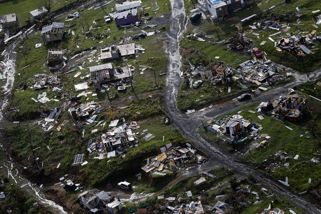 """Debris scatters a destroyed community in the aftermath of Hurricane Maria in September in Toa Alta, Puerto Rico. Still recovering from Hurricane Maria, Puerto Rico is getting a helping hand from an unlikely source, Moe from """"The Simpsons."""""""