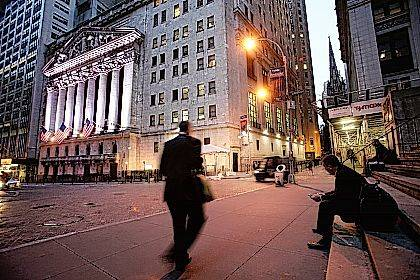 FILE - In this Oct. 8, 2014, file photo, a man walks to work on Wall Street, near the New York Stock Exchange, in New York. Global stocks mostly fell on Monday, Nov. 6, 2017, and the price of oil hit a two-year high after a spate of high-profile arrests in Saudi Arabia unnerved some investors and suggested the kingdom could be more bullish in pursuing output cuts. (AP Photo/Mark Lennihan, File)