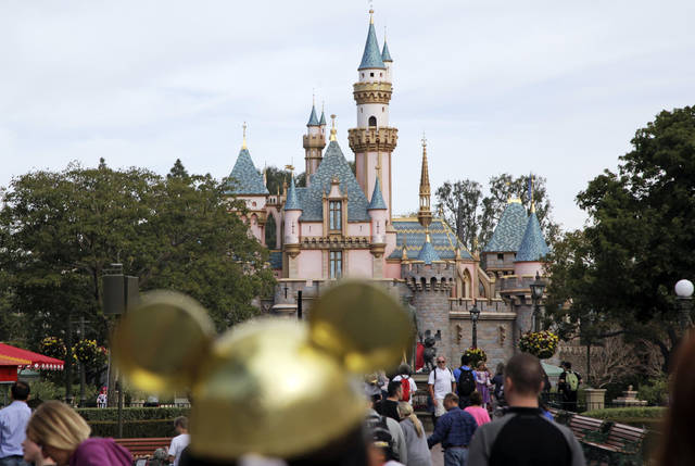 Visitors walk toward the Sleeping Beauty's Castle in the background at Disneyland Resort in 2015 in Anaheim, Calif. Four prominent film critics groups announced Tuesday they will bar Walt Disney Co. films from receiving awards consideration over the company's decision to keep the Los Angeles Times from advance screenings of its films and access to its talent.
