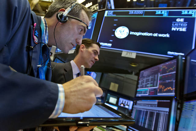 Trader Gregory Rowe, left, and specialist John McNierney work at the post that handles General Electric on the floor of the New York Stock Exchange, Tuesday, Nov. 14, 2017. Stocks are opening lower on Wall Street as technology companies, banks and retailers sink. (AP Photo/Richard Drew)