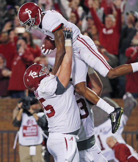Alabama offensive lineman Bradley Bozeman (75) hoists wide receiver DeVonta Smith (6) as they celebrate Smith's 26-yard touchdown pass reception for the go-ahead score during the fourth quarter of an NCAA college football game in Starkville, Miss., Saturday, Nov. 11, 2017. Alabama won 31-24. (AP Photo/Rogelio V. Solis)