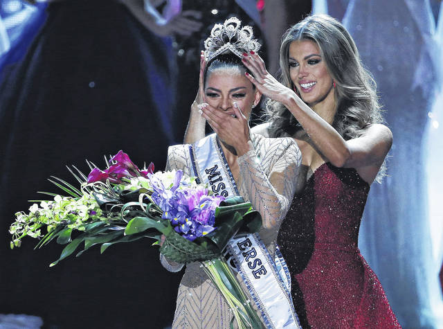 Former Miss Universe Iris Mittenaere, right, crowns new Miss Universe Demi-Leigh Nel-Peters at the Miss Universe pageant Sunday in Las Vegas.