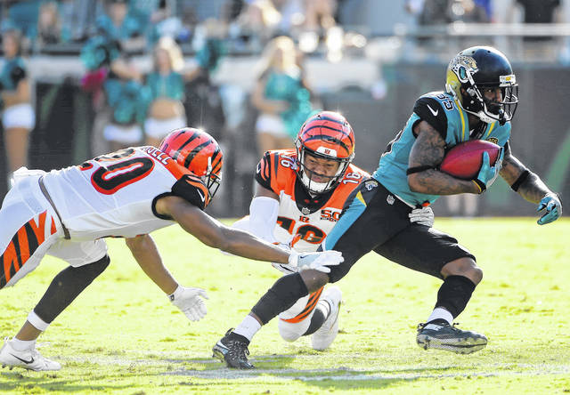 Jacksonville Jaguars' Jaydon Mickens, right, slips past Cincinnati Bengals cornerback KeiVarae Russell (20) and wide receiver Cody Core (16) en route to a 63-yard touchdown on a punt return during the second half of an NFL football game, Sunday, Nov. 5, 2017, in Jacksonville, Fla. (AP Photo/Phelan M. Ebenhack)