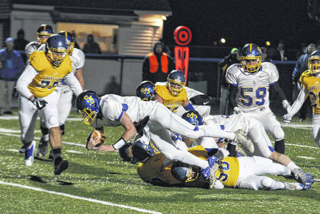 Jared Wurst of Delphos St. John's dives for a first down while being tackled by Lehman Catholic's Logan Richard during Friday night's playoff game at Allen East High School.