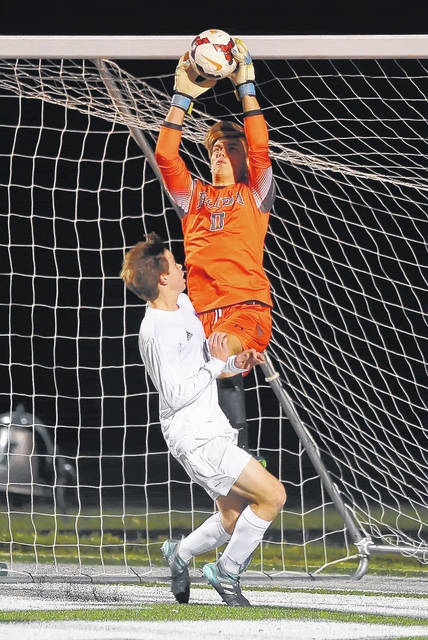 Elida goalie Caleb Jones makes a save in front of Bay's Kyle Cusimano during Saturday's Division II regional final at Mansfield Madison.