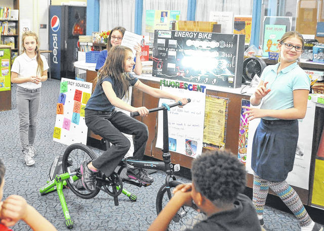 Kayla Mills, 10, left, Jurisha Houseworth, 11, and Abigail Antus, 11, watch Montana Clampit, 11, pedal the energy bike to transform mechanical energy to electricity during a presentation to Lima North Middle School on Friday.