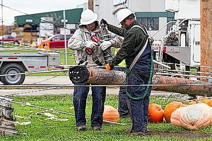 In the white is JJ Tester, alongside fellow co-worker of The Wapak City Light Department Mike Sparks. Both men were still working at 10 a.m. Monday after being called to the scene of Celina at 7 p.m. Sunday.