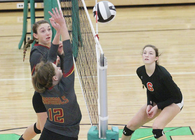 New Bremen's Rachel Kremer, left, and Claire Pape (12) go up to block as Fort Loramie's McKenzie Hoelscher waits for the ball to come back across the net during Saturday's Division IV regional final at Northmont.