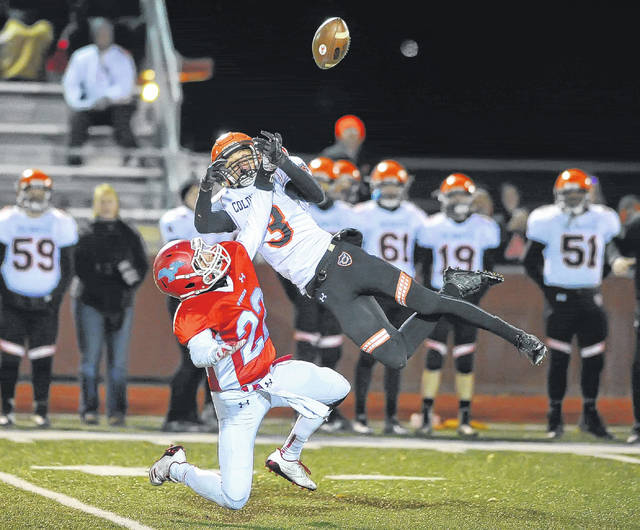 Lima Central Catholic's Brayden O'Dell, left, and Coldwater's Jack Muhlenkamp battle for a pass during Friday night's playoff game at Harmon Field in Wapakoneta.