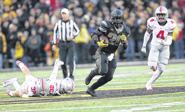 Iowa's James Butler leaves Ohio State's Tuf Borland (left) and Dante Booker on the ground and is pursued by Jordan Fuller (4) during a 53-yard third-quarter run during Saturday's game in Iowa City, Iowa. See more game photos at LimaScores.com