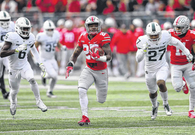Ohio State's Mike Weber leaves Michigan State's David Dowell (6) and Khari Willis behind on his way to scoring a touchdown during Saturday's game at Ohio Stadium in Columbus. See more game photos at LimaScores.com.