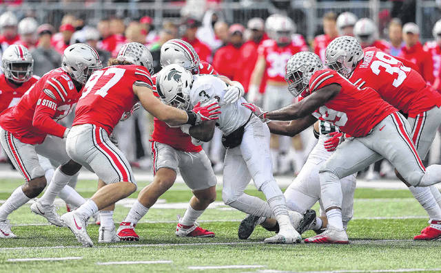 Michigan State's LJ Scott is surrounded by Ohio State defenders during Saturday's game at Ohio Stadium in Columbus.
