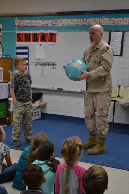 """Submitted photo Second-grade students at Crestview Elementary School recently welcomed military veteran Doug Dye into their classroom. Dye shared with students some stories of his deployments to Iraq, his medals and other honors. The students also enjoyed looking at Dye's military """"money."""""""