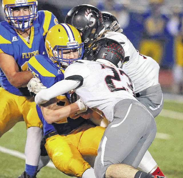 Spencerville's Logan Rex, left, and Connor Holmes join forces to stop Marion Local's Brandon Fleck during Friday night's playoff game at Piqua.