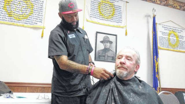 Leandra Johnson of Fresh N Faded gives a free haircut to veteran Chuck Hahn during the Stand Down for Veterans event Friday at the American Legion Post 96.