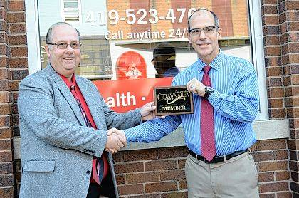 Bryan Reynolds | The Lima News Local State Farm Insurance Agent Garry Peterson (left) accepts a Ottawa Area Chamber of Commerce plaque from Barney Beckan, of Beckman Jewlers, during the ribbon cutting for the new State Farm Insurance office at 125 W. Main St. Suite B, Ottawa.