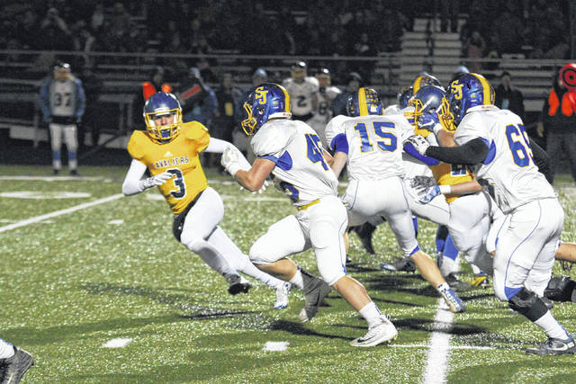 Troy Schwinnen of Delphos St. John's for yardage as Lehman Catholic's RJ Bertini looks to cut him off during Friday night's playoff game at Allen East High School.