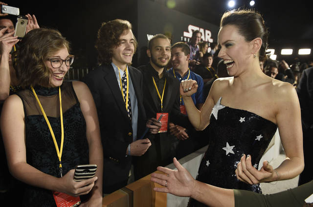 "Daisy Ridley, right, a cast member in the film ""Star Wars: The Last Jedi,"" laughs with Shannon McNabb, from left, Tyler Woodward and Chris Alegria at the premiere of the film Dec. 9 at the Shrine Auditorium in Los Angeles. The teens were among seven teens with life-threatening medical conditions who were among the special guests at the premiere as part of the Make-A-Wish Foundation."
