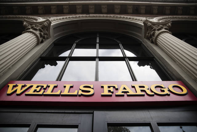 FILE - This Friday, Aug. 11, 2017, file photo shows a sign at a Wells Fargo bank location in Philadelphia. Wells Fargo stands to benefit from the new tax overhaul. (AP Photo/Matt Rourke, File)