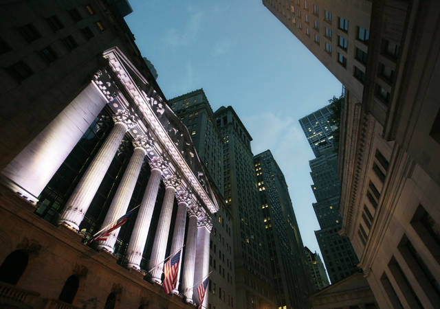 FILE - In this Wednesday, Oct. 8, 2014, file photo, American flags fly in front of the New York Stock Exchange. World stock markets were mixed on Thursday, Dec. 28, 2017, in quiet post-Christmas holiday trading. Strong economic data from Asia and the U.S. boosted investor confidence in some markets. (AP Photo/Mark Lennihan, File)