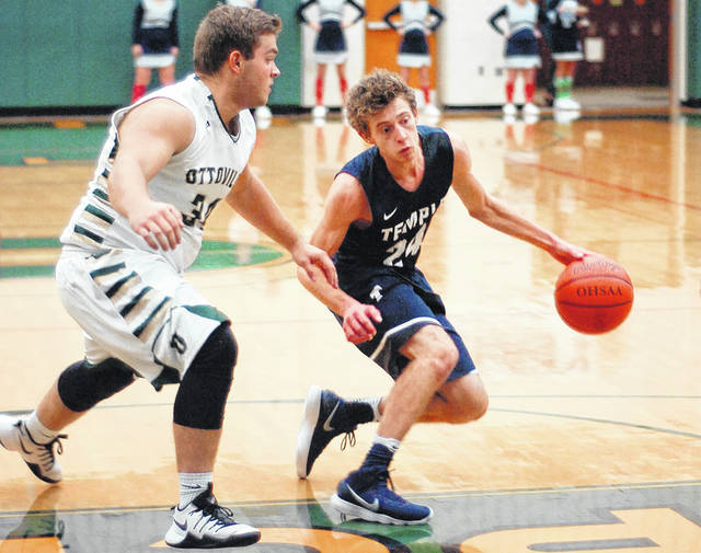 Ottoville's Zane Martin guards Temple Christian's Brody Bowman during Friday night's game at Ottoville High School.