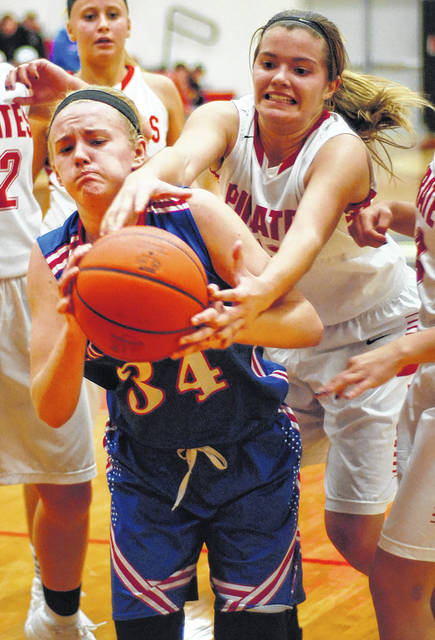 Crestview's Paige Motycka (34) and Bluffton's Averey Rumer battle for a rebound during Thursday night's game in Bluffton.