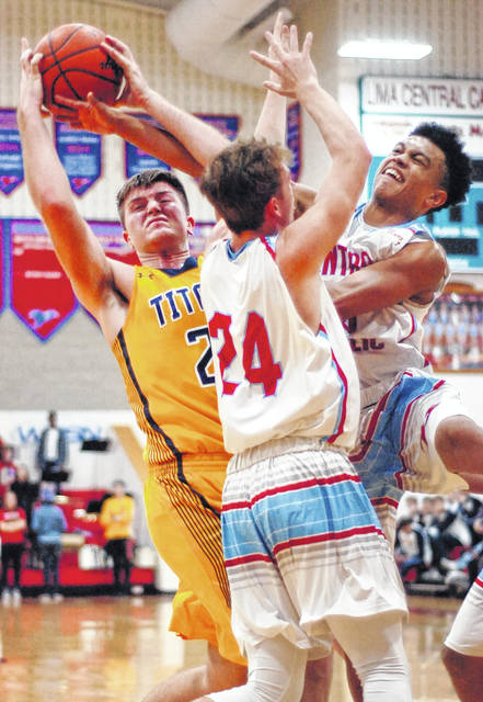 Ottawa-Glandorf's Jake Dible, left, fights for the rebound against Lima Central Catholic's Raoul Samaroo, right, and Brendan Stolly during Saturday night's game at LCC. See more game photos at LimaScores.com