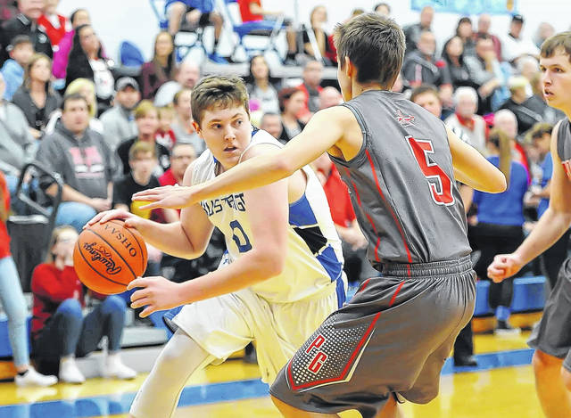 Allen East's Grant Whitley drives against Pandora-Gilboa's Cooper McCullough during Wednesday night's game at Allen East High School. P-G won the game 68-31. No other information was reported about the game at deadline.