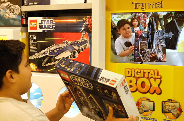 Koby Merlos holds up a Star Wars Lego set to a screen that employs augmented reality technology to bring boxes to life digitally, showing how the sets will look when built.