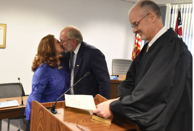 Mayor David Berger kisses his wife, Linda, after being sworn in for his eighth term as mayor of the City of Lima. Far right is Judge Jeffrey Reed of Allen County Common Pleas Court.