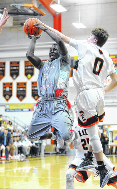 Lima Central Catholic's Jaron Banks goes up for a shot against Elida's Matt Fish during Saturday night's Mercy Health-St. Rita's Tip-Off Classic at Elida.
