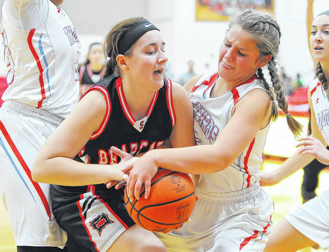Spencerville's Abbygayle Satterfield (left) fights for the ball with Lima Central Catholic's Josie Mohler (right) during Monday's game at Msgr. Edward C. Herr Gymnasium.