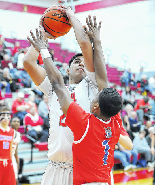 Lima Senior's Jatsiel Colon puts up a shot against St. Francis' Tayler McNeal during Tuesday night's game at Lima Senior High.