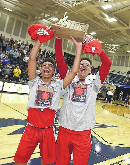 Perry's Orion Monford, left, and Koby Glover hoist the regional championship trophy the Commodores won while wearing Perry Strong shirts in rememberance of assistant coach Herb Lane Jr. who died in a vehicle crash.