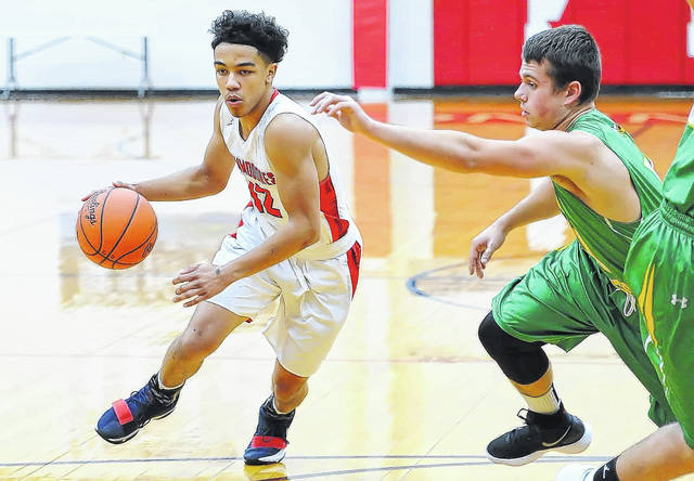 Perry's Jamal Whiteside drives against Cory Rawson's Nathan Zuercher during Tuesday night's game at Perry's Leonard V. Volbert Gymnasium.
