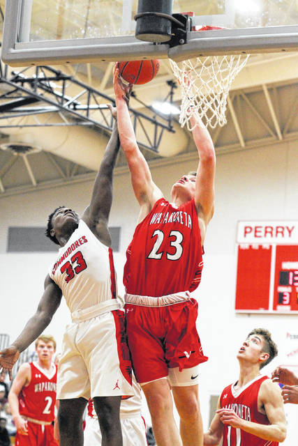 Wapakoneta's Adam Scott goes up for a rebound against Perry's Martell White during Thursday night's game at Perry.