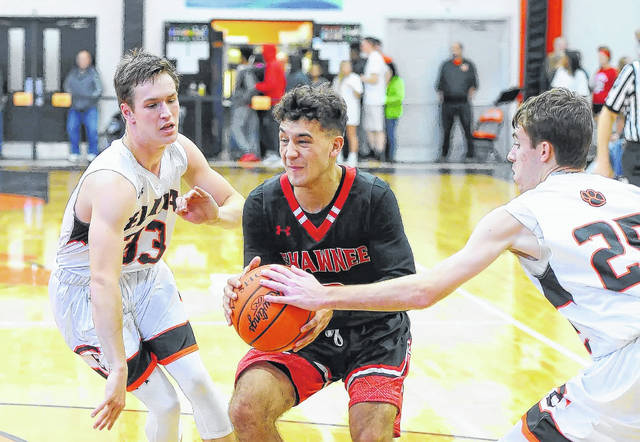 Shawnee's Riley Rosado drives against Elida's Daniel Unruh, left, and Skyler Smith during Friday night's Mercy Health-St. Rita's Tip-Off Classic at Elida.