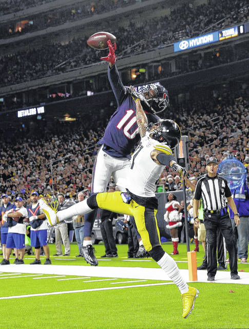 Houston Texans wide receiver DeAndre Hopkins (10) catches a pass for a touchdown as Pittsburgh Steelers cornerback Joe Haden (21) defends during the second half of an NFL football game Monday, Dec. 25, 2017, in Houston. (AP Photo/Michael Wyke)