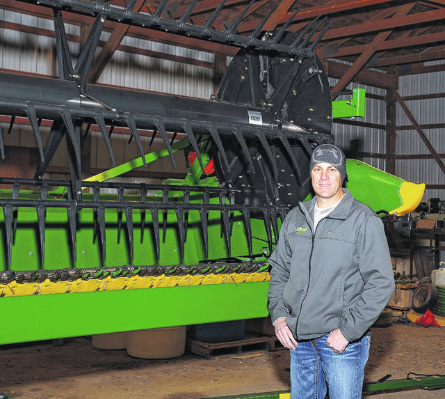 Allen County Sheriff Matt Treglia stands alongside his farm equipment in his barn in eastern Allen County. Treglia began working on the farm when he was 9, following in the footsteps of his grandfather and father.