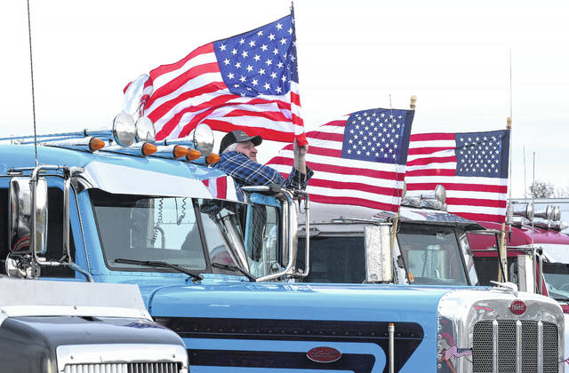 Truck driver Luke Daugherty, of Zanesville, decorates his truck with an American flag while parked across from U.S. Rep. Jim Jordan's Lima office on Elm Street during a protest Monday morning. Nearly 50 truckers in Lima called for a delay in implementing the installation of electronic logging devices, which are set to replace manual paper logs.