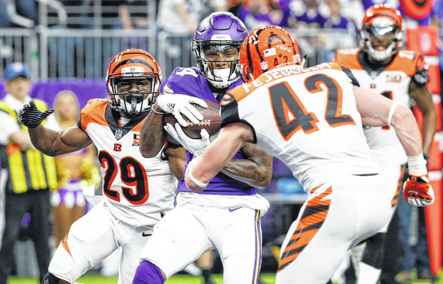 Minnesota Vikings wide receiver Stefon Diggs, center, catches a 20-yard touchdown pass between Cincinnati Bengals defenders Tony McRae, left, and Clayton Fejedelem, right, during the first half of an NFL football game, Sunday, Dec. 17, 2017, in Minneapolis. (AP Photo/Bruce Kluckhohn)
