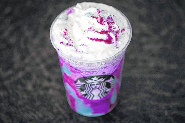 """FILE - In this April 20, 2017, file photo, a Starbucks Unicorn Frappuccino is displayed in Philadelphia.  It """"magically"""" started as a purple drink with swirls of blue and a first taste that is sweet and fruity, according to the company. (AP Photo/Matt Rourke, File)"""
